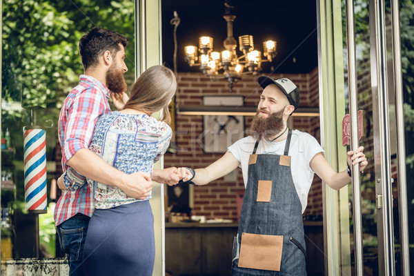 Cool hairstylist giving a fist bump to a happy customer at the door Stock photo © Kzenon