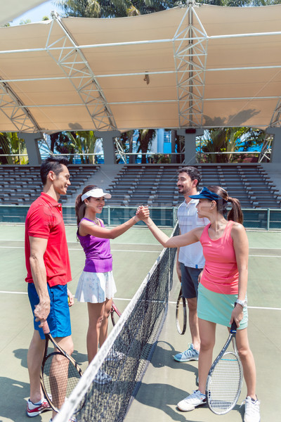 Four young tennis players putting hands together before a doubles match Stock photo © Kzenon