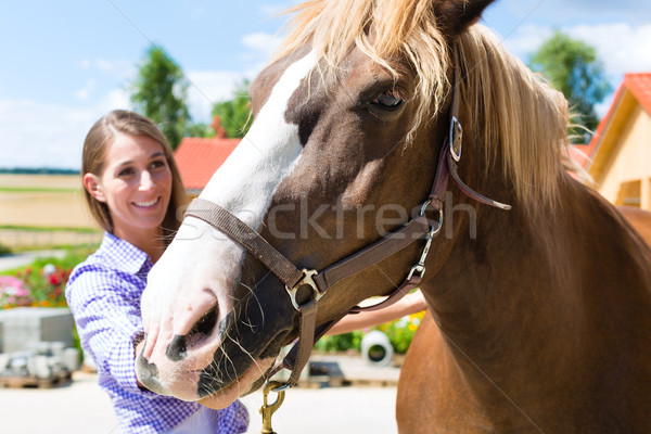 Young woman in the stable with horse and is happy Stock photo © Kzenon