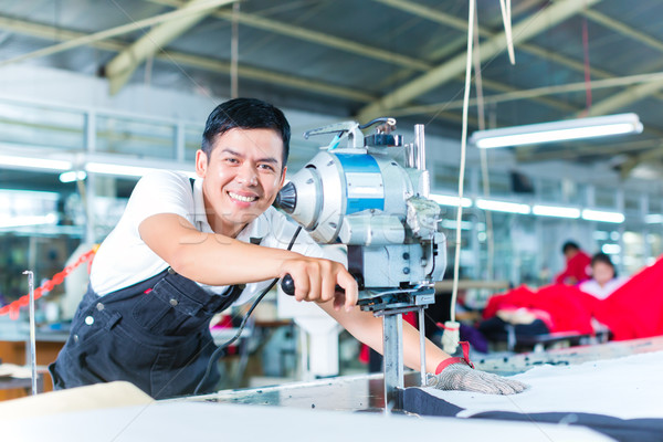 Asian worker using a machine in a factory Stock photo © Kzenon