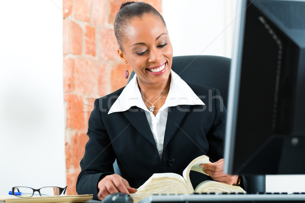Stock photo: Lawyer in office with law book and computer