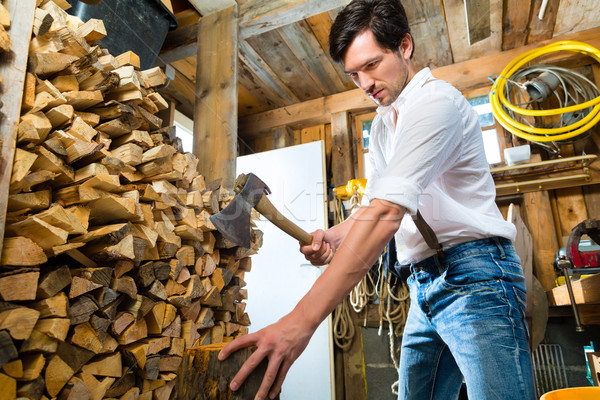 Young man chopping fire wood in mountain chalet Stock photo © Kzenon