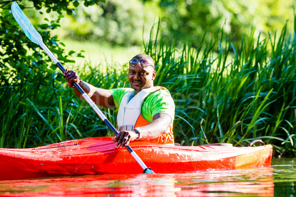 African Man paddling with canoe on forest river Stock photo © Kzenon