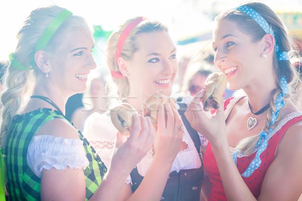 Friends eating grilled sausage at Oktoberfest Stock photo © Kzenon