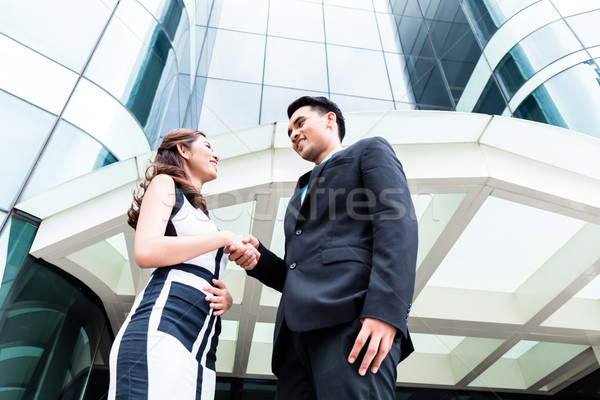 Asian businesspeople handshake in front of high rise building Stock photo © Kzenon
