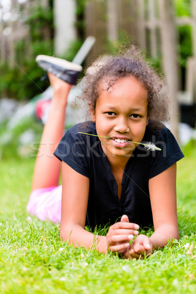 Black girl lying with grass blade on meadow Stock photo © Kzenon