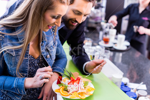 Woman eating fruit sundae in ice cream cafe Stock photo © Kzenon