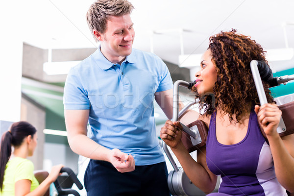 African woman in gym exercising with personal trainer Stock photo © Kzenon