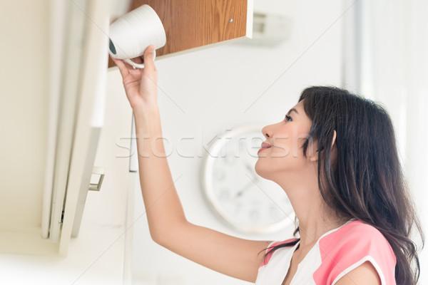 ázsiai nő csészék konyhaszekrény munka dolgozik Stock fotó © Kzenon
