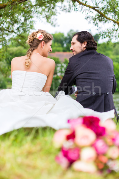 Bridal pair with bouquet sitting on meadow Stock photo © Kzenon