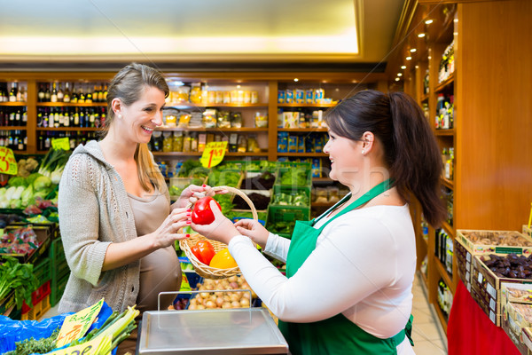 Sales lady handing vegetables to woman in grocer store Stock photo © Kzenon
