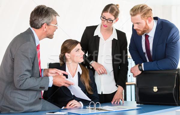 Team gathers around a desk, discussing a document Stock photo © Kzenon