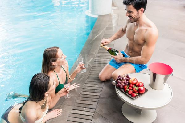 Junger Mann Servieren Champagner zwei Frauen Schwimmbad verführerisch Stock foto © Kzenon