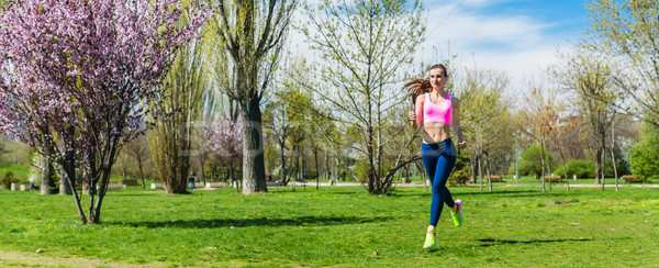 Woman running for better fitness though a park in spring Stock photo © Kzenon