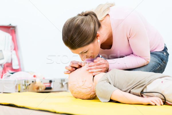 Woman in first aid course practicing revival of infant on baby d Stock photo © Kzenon