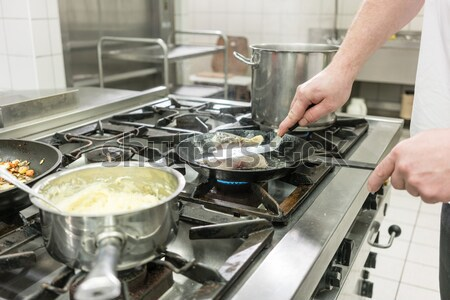 Chef using pincers to bone carp fish filet frying on oven in kit Stock photo © Kzenon