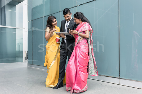 Indian business people using high-tech devices during break Stock photo © Kzenon