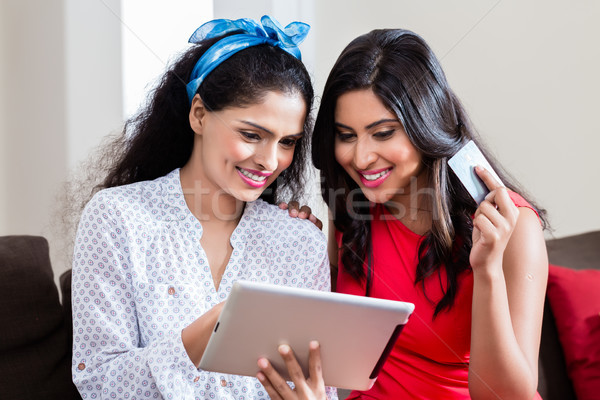 Two women using a tablet PC for online payment Stock photo © Kzenon