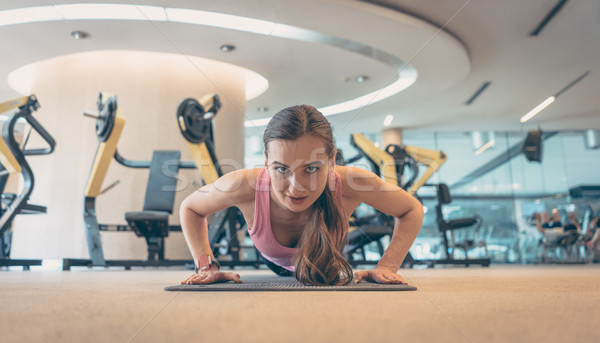 Woman doing push-up in gym for better fitness Stock photo © Kzenon