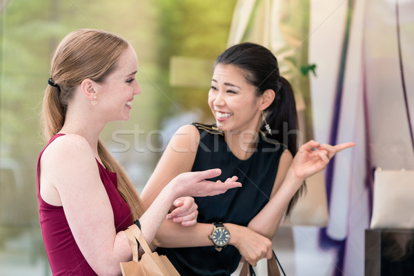Two fashionable women carrying paper bags while shopping in summ Stock photo © Kzenon