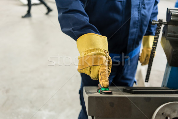 Hand of a worker pressing the button of an industrial machine Stock photo © Kzenon