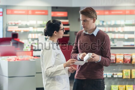 Experienced pharmacist checking the indications of a medicine ne Stock photo © Kzenon