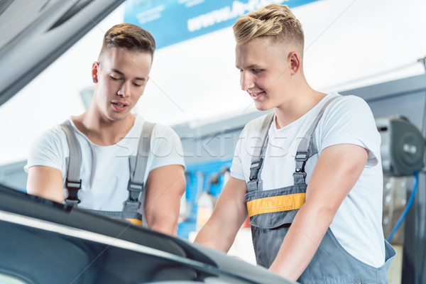 Experienced auto mechanic checking the parts of a car in a moder Stock photo © Kzenon