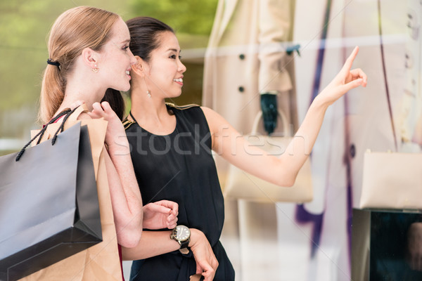 Two fashionable women carrying paper bags while shopping in summer Stock photo © Kzenon