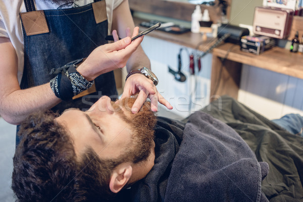 Bearded young man ready for shaving in the hair salon of a skilled barber Stock photo © Kzenon
