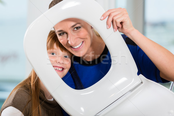 Portrait of a woman and her daughter looking at camera through a toilet seat Stock photo © Kzenon