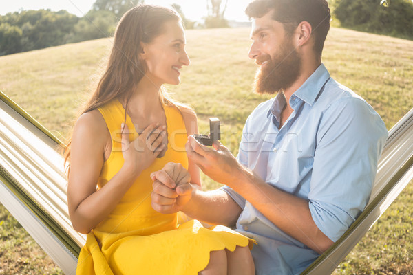 Young man making marriage proposal to beautiful girlfriend outdoors Stock photo © Kzenon