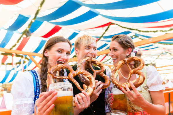 Friends eating giant pretzels and drinking in beer tent Stock photo © Kzenon