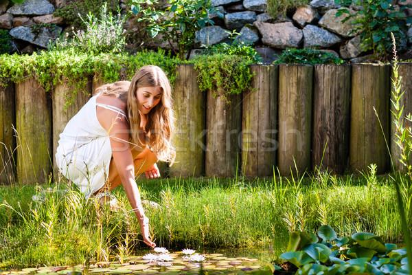 Woman sitting at pond in her garden Stock photo © Kzenon