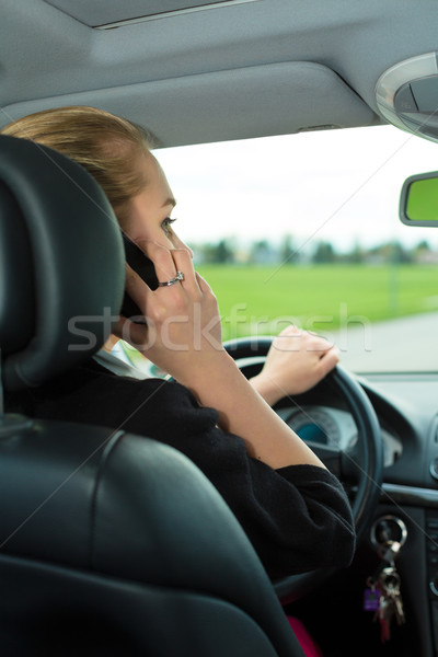 Young woman with telephone in car Stock photo © Kzenon