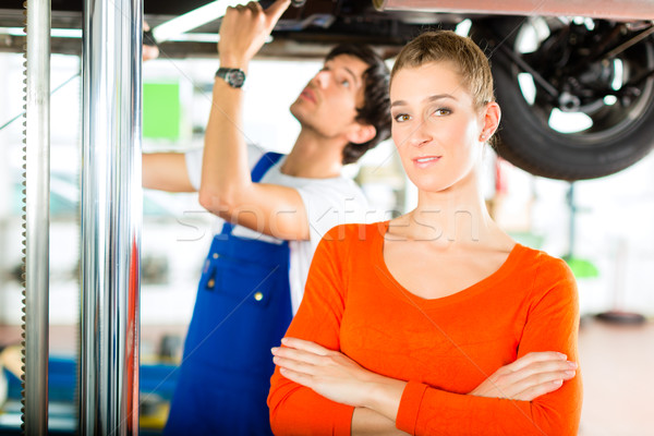 Car Mechanic repairing auto of woman customer Stock photo © Kzenon