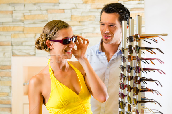 Young couple at optician with glasses Stock photo © Kzenon