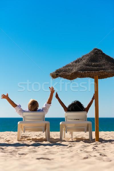 Сток-фото: счастливым · пару · пляж · сидят · солнце · стульев