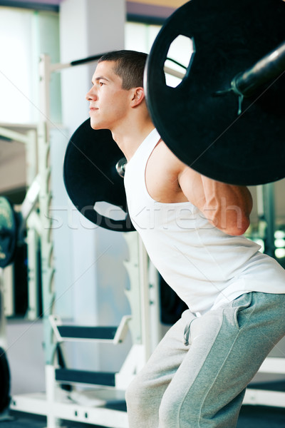Man lifting weights in gym Stock photo © Kzenon