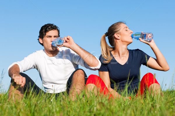 Jogger couple resting and drinking water Stock photo © Kzenon