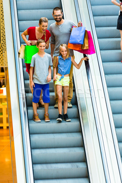 Stock photo: Family in shopping mall on escalators with bags