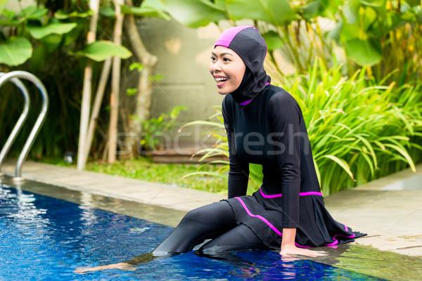 Muslim woman wearing Burkini swimwear at pool Stock photo © Kzenon