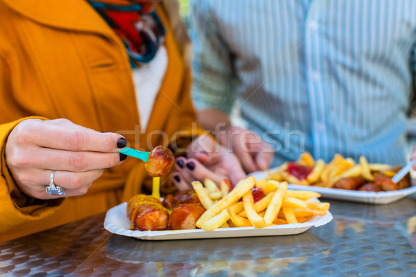 Couple eating German Currywurst at stand Stock photo © Kzenon