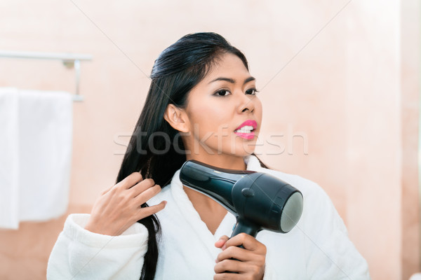 Asian woman in bathroom drying hair Stock photo © Kzenon