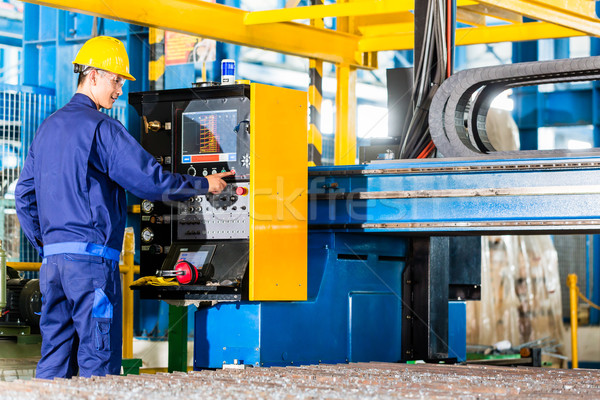 Worker in manufacturing plant at machine control panel Stock photo © Kzenon