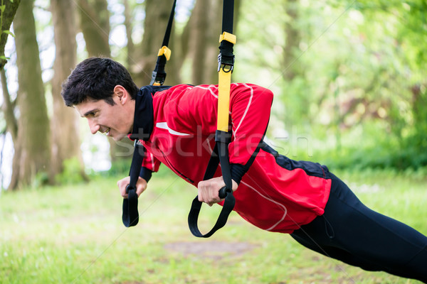 Man doing fitness sling training outdoors Stock photo © Kzenon