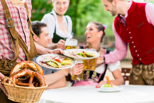 Waiter serving food in Bavarian beer garden Stock photo © Kzenon