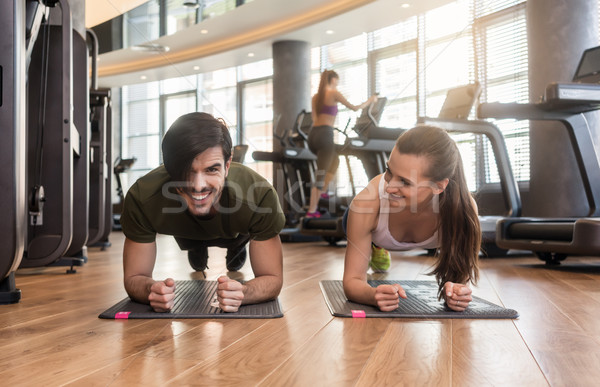 Cheerful young couple exercising forearm plank during workout in Stock photo © Kzenon