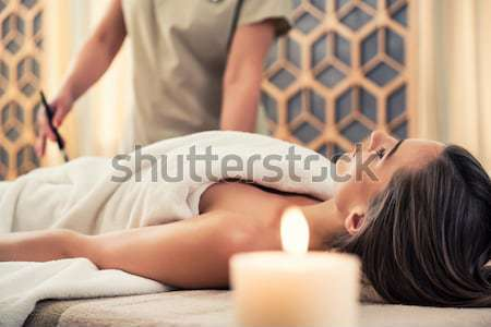 Asian therapist applying manually rejuvenating lotion at luxury  Stock photo © Kzenon