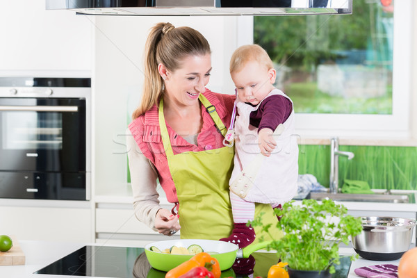 Mum cooking with baby in arm  Stock photo © Kzenon