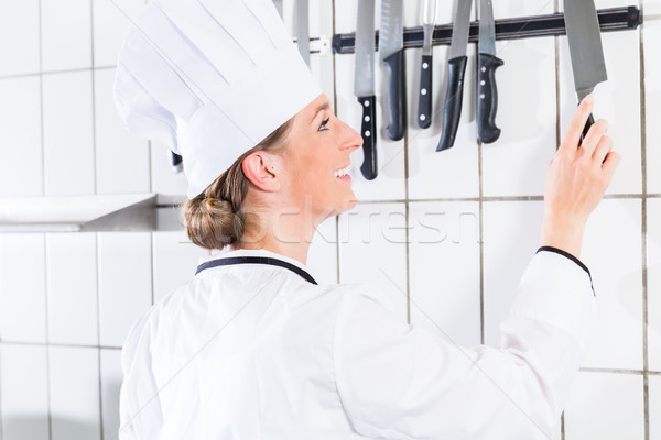 Stock photo: Female chef in industrial kitchen taking knife from wall bracket